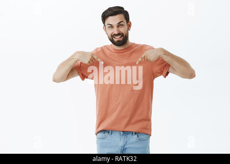 Portrait of satisfied good-looking carefree dark-haired bearded male in 30s, pointing down or t-shirt with happy and joyful smile gazing at camera showing cool product over gray background - Stock Photo
