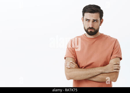Waist-up shot of lonely and gloomy displeased cute european guy in casual t-shirt crossing arms on chest frowning squinting looking left offended and sad standing gloomy and insulted over gray wall. - Stock Photo