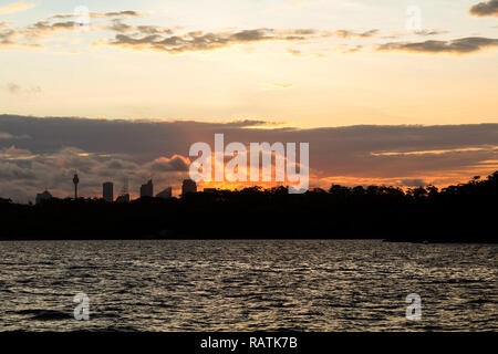 Dramatic sunset behind the skyline of Sydney as seen from Manly ferry on a warm summer evening (Sydney, New South Wales, Australia) - Stock Photo