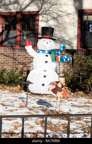 House decorated with a waving top hatted wooden snowman wearing a blue scarf, red mittens and carrying a gift. St Paul Minnesota MN USA - Stock Photo