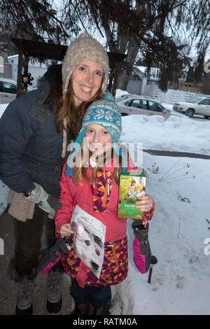Mother and daughter selling Girl Scouts cookies door to door in winter weather. St Paul Minnesota MN USA - Stock Photo
