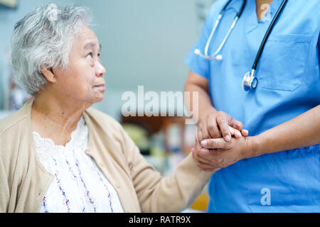Holding Touching hands Asian senior or elderly old lady woman patient with love, care, helping, encourage and empathy at nursing hospital ward.