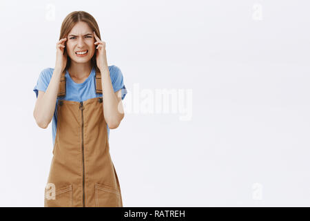 Girl cannot understand what happening being unfocused thinking hard holding hands on temples squinting and clenching teeth trying solve problem thinking intense over gray background - Stock Photo