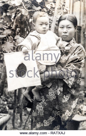 young adult woman in traditional kimono standing with toddler baby ca 1930s Japan - Stock Photo