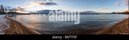 Sunset on the shoreline of south Lake Tahoe, Sierra Mountain peaks covered in snow visible in the background, California - Stock Photo
