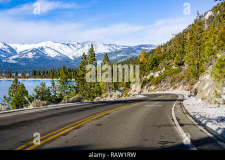 Travelling on the shoreline of Lake Tahoe on a winter day; Sierra mountains covered with snow visible in the background - Stock Photo
