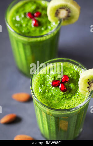Green smoothie with kiwi, apple, spinach, banana and almond milk close up decorated with pomegranate grains - Stock Photo