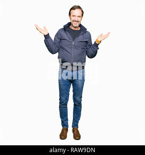 Middle age handsome man wearing a jacket Smiling showing both hands open palms, presenting and advertising comparison and balance - Stock Photo