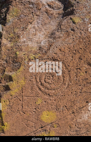 Petroglyph with spiral design carved into sandstone by Ancestral Puebloan People at the Tsankawi Prehistoric Sites in Bandelier National Monument near - Stock Photo
