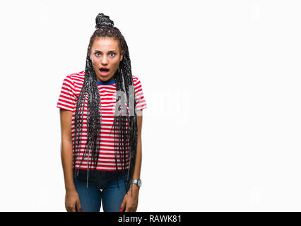 Young braided hair african american girl over isolated background afraid and shocked with surprise expression, fear and excited face. - Stock Photo