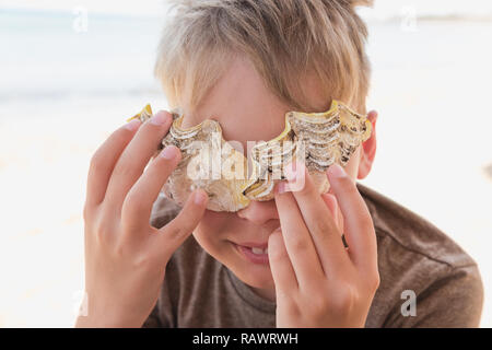 Cute happy smiling white kid holding yellow seashells near eyes smiling. Playful tanned caucasian boy hiding behind sea shells cheerfully. Horizontal  - Stock Photo