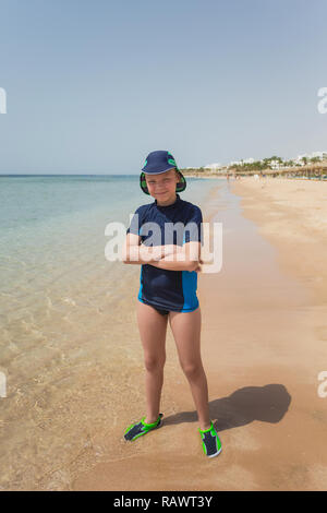 Portrait of happy smiling young caucasian tanned kid standing on sunny sandy beach in Egypt. Vertical color photo of boy in full length. Child wearing - Stock Photo