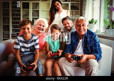 Family enjoying video game in living room - Stock Photo