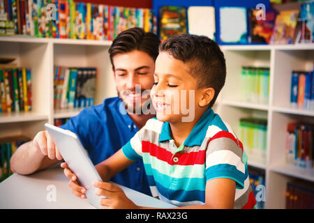 Teacher and student using digital tablet in library