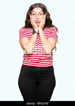 Young beautiful woman wearing glasses Tired hands covering face, depression and sadness, upset and irritated for problem - Stock Photo