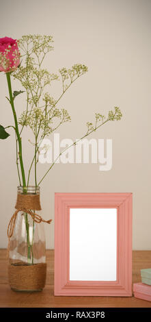 Rose flower in glass vase, photo frame and gift boxes on a table - Stock Photo