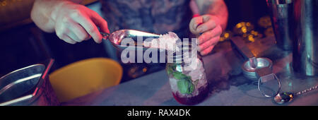 Bartender putting ice in jar while preparing cocktail - Stock Photo