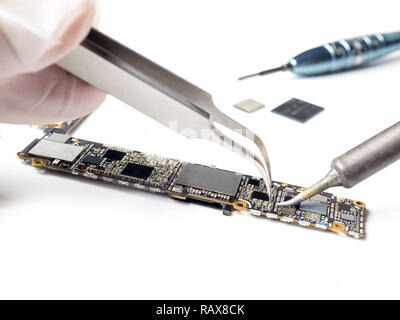 Close-up image of technician replacing microchip of smartphone logic board - Stock Photo