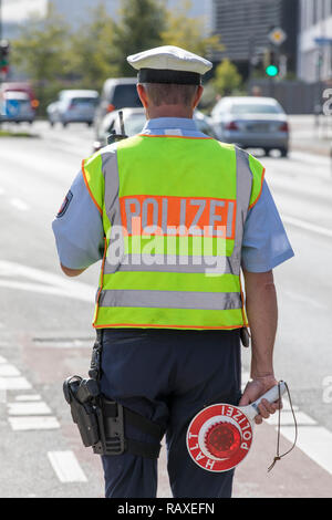Policeman with yellow safety vest and stopping trowel, during a traffic control, Germany, - Stock Photo
