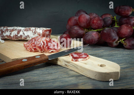 Sliced dry cured Fuet sausage and red grapes on wooden cutting board with sharp knife - Stock Photo