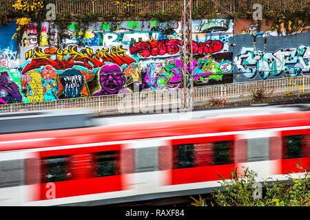 graffiti paintings, on a concrete wall at a railroad track near the central station, rapid-transit railway, Germany, Essen, - Stock Photo