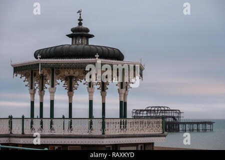 Victorian bandstand on the promenade in Brighton, East Sussex, UK. Seagull sits atop.The remains of West Pier can be seen in the background. - Stock Photo