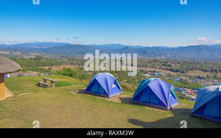 Three tents of blue on the high hills. Background blue sky and  mountain. - Stock Photo