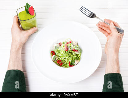 Man holding green smoothie and eating Raw vegan spaghetti from zucchini, sun dried tomatoes and nut cheese on white background in restaurant Stock Photo