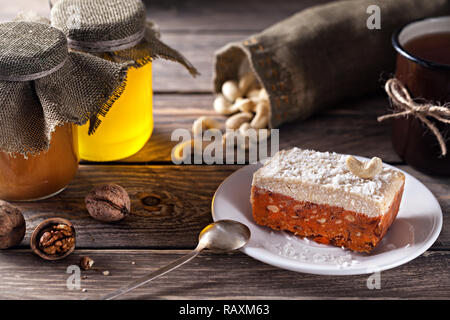 Raw vegan cake from carrot, walnuts and cashew coconut cream on the top near honey jars and tea mug - Stock Photo