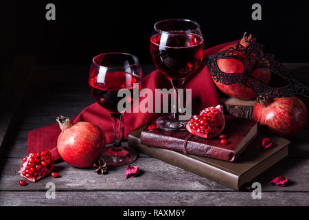 Fresh pomegranate juice in wine glasses near fruits, books and black woman mask on rustic wooden background with space for text Stock Photo