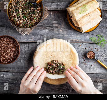Woman rolling Russian vegan pancakes with buckwheat and Laminaria served in rustic style on Shrovetide holidays - Stock Photo