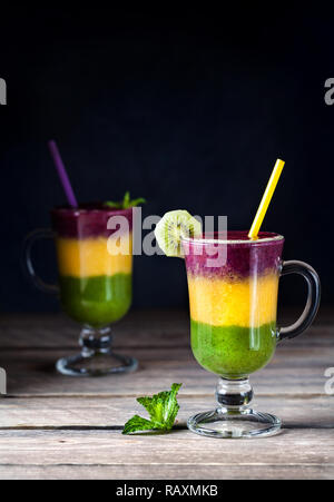 Two smoothie with colorful layers from kiwi, oranges and blackberry on wooden background - Stock Photo