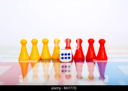 Picture of red and yellow pawns with dice on the ludo board game. - Stock Photo