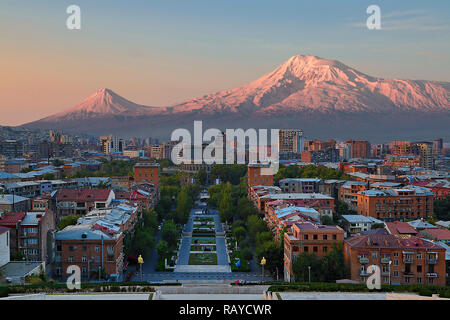 View over the city of Yerevan, capital of Armenia, with the two peaks of the Mount Ararat in the background, at the sunrise - Stock Photo