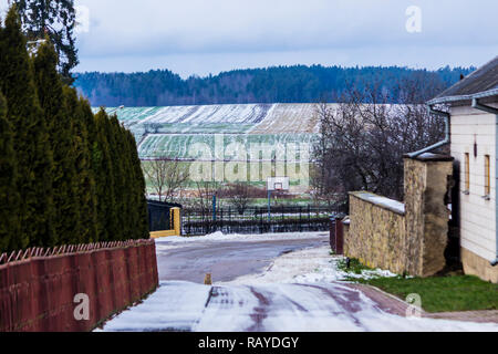 Street in the village. There is a bit of snow on the green meadows and plowed fields. Forest in the background. The beginning of winter in Europe. - Stock Photo