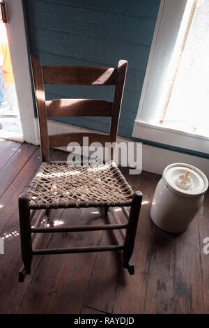 Antique woven cane chair with butter churn on wooden floor in Historic Texan Home, Chestnut Square Historic Village, McKinney, Texas. - Stock Photo