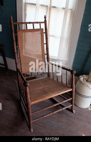 Antique woven cane rocking chair with butter churn on wooden floor in Historic Texan Home, Chestnut Square Historic Village, McKinney, Texas. - Stock Photo