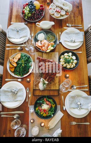 Modern Australian Christmas dinner table with glazed ham, prawns, potatoes and dill, asian greens, Christmas pudding, minced fruit pies by candlelight - Stock Photo