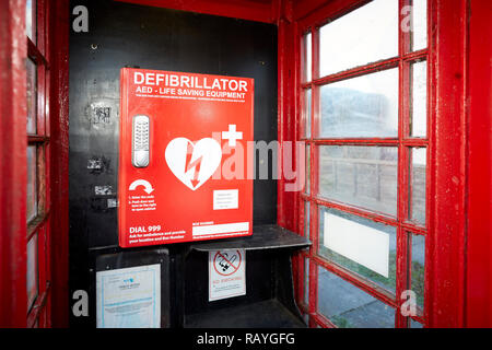 Emergency defibrillation automated external defibrillator (AED) located in an old red telephone box in a Lancashire Village - Stock Photo