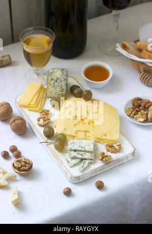 Appetizers of various types of cheese, grapes, nuts and honey, served with white and red wine. Rustic style. - Stock Photo