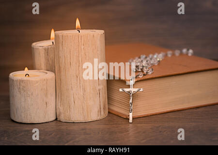 Silver rosary and crucifix resting on closed book near the candles on wooden table, religion school concept. Vintage style. - Stock Photo