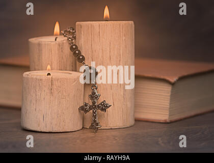 black rosary and crucifix resting on closed book near the candles on wooden table, religion school concept. Vintage style. - Stock Photo