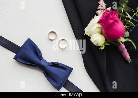 Close up top view of elegant modern formal male accessories. Blue bowtie, two golden wedding rings, flower boutonniere pinned to black jacket of suit. - Stock Photo