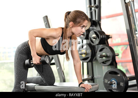 Cute girl has a hard athletic workout in the gym, doing exercises with barbells. - Stock Photo