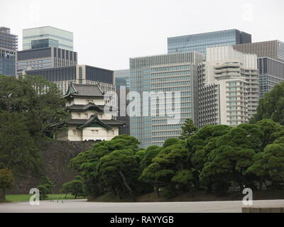 Dwarfed by modern office blocks, one of the old guard towers atop the stone walls of the moat; Imperial Palace East Gardens, Tokyo, Japan - Stock Photo