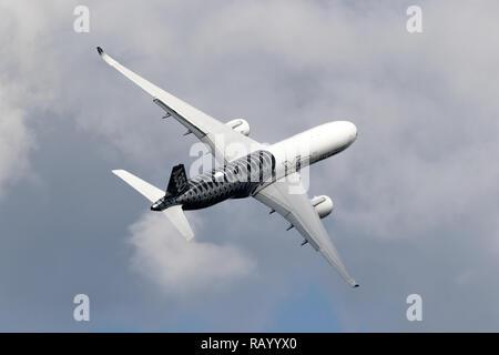 BERLIN - APR 27, 2018: New Airbus A350 XWB passenger jet plane in flight at the Berlin ILA Air Show. - Stock Photo