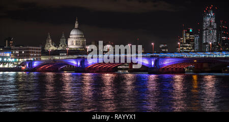 Panoramic photo of the London skyline at night, showing River Thames, Blackfriars Bridge illuminated, commercial buildings and St Paul's Cathedral - Stock Photo