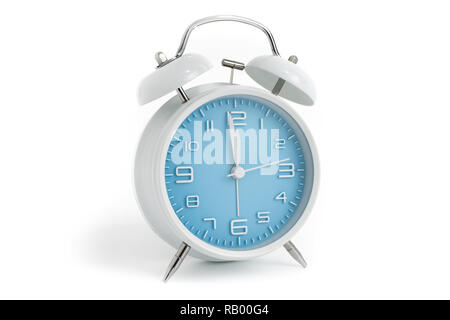 Table alarm clock with time 1 minute to 12 hours with blue clock face, 11.59 AM PM, on white background - Stock Photo