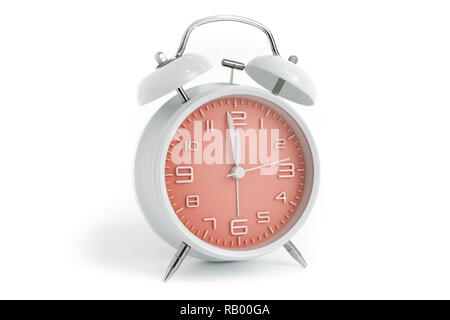 Table alarm clock with time 1 minute to 12 hours with orange clock face, 11.59 AM PM, on white background - Stock Photo