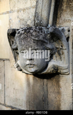 Ecclesiastical sculpture of an angelic face caved in stone decorating the entrance to a church, Eaton Socon, UK. - Stock Photo